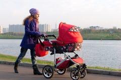 Mutter mit einem Kinderwagen Stockbild