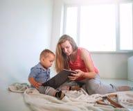 Mutter mit einem kleinen Babysohn im Raumlesebuch zu Hause stockfoto