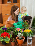 Mutter mit einem Kleinkind im Raum mit Blütenpflanzen in den Töpfen Lizenzfreie Stockfotografie