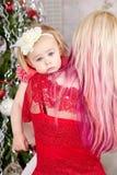Mutter mit einem müden Baby vor Weihnachtsbaum Weihnachtsfamilien-Porträt lizenzfreie stockfotos