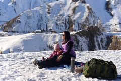 Mutter mit einer kleinen Tochter im Winter auf einem Picknick in den Bergen lizenzfreie stockfotos