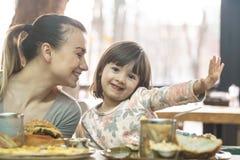 Mutter mit einer netten Tochter, die Schnellimbiß in einem Café isst lizenzfreie stockfotografie