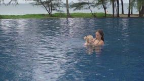 Mutter mit einer zweijährigen Tochter im Hotelpool nahe Ozean stock footage