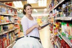 Mutter mit elektronischer Einkaufsliste Stockfoto