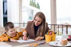 Mutter mit farbigen Bleistiften des Jungen abgehobener Betrag Stockfotografie
