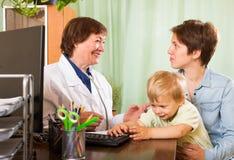 Mutter mit hörendem freundlichem Kinderarztdoktor des Babys Lizenzfreie Stockbilder