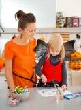 Mutter mit Halloween kleidete blonde Mädchenzeichnung Jack-O-Laterne Stockfotos