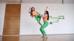 Mutter mit ihrem übenden modernen Yoga der Tochter wirft auf stock footage