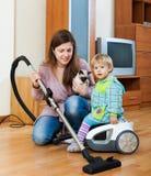 Mutter mit ihrem Baby, das Hausreinigung im Raum tut Lizenzfreies Stockfoto