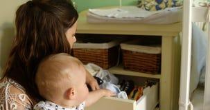 Mutter mit ihrem Baby, das Kleidung im Fach 4k schaut stock video