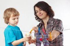 Mutter mit ihrem hängenden Spielzeug des kleinen Sohns Stockbild