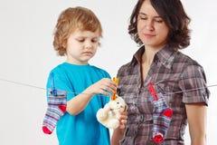 Mutter mit ihrem hängenden Spielzeug und Kleidung des kleinen Sohns Stockfotos