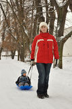 Mutter mit ihrem Kind auf Schlitten Stockfotografie