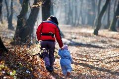 Mutter mit ihrem Kind, das in den Wald geht Stockfotografie