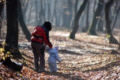 Mutter mit ihrem Kind, das in den Wald geht Lizenzfreie Stockfotos