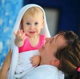 Mutter mit ihrem Kind im Bademantel Lizenzfreie Stockfotografie