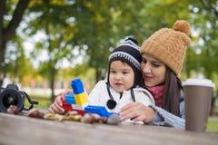 Mutter mit ihrem Kinderspiel im Park, der mit Blöcken spielt stockfoto