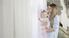 Mutter mit ihrem kleinen Baby, das nahe dem Fenster steht und draußen schaut stock video footage