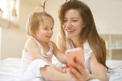 Mutter mit ihrem kleinen Baby, das Spaß im Bett hat Unter Verwendung intelligenten p Lizenzfreie Stockfotografie