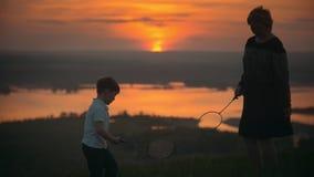 Mutter mit ihrem kleinen Sohn, der Badminton auf dem Hügel bei Sonnenuntergang spielt stock video