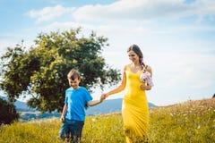 Mutter mit ihrem Sohn, der auf einer Sommerwiese läuft Stockfotos