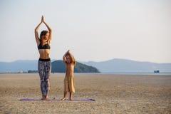 Mutter mit ihrem Sohn, der Yoga tut Lizenzfreie Stockfotos