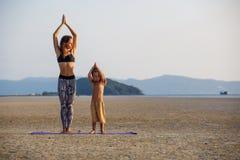 Mutter mit ihrem Sohn, der Yoga tut Stockfotos