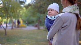 Mutter mit ihrem Sohn in ihren Armen gehend in den Park Nahaufnahme stock footage