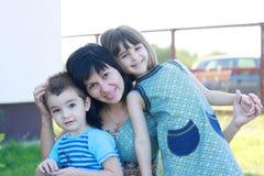 Mutter mit ihrem Sohntochterlächeln Stockfotos