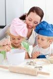 Mutter mit ihren Kindern, die zusammen backen stockfotos
