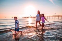 Mutter mit ihren Söhnen, die auf dem Ufer spielen stockbild
