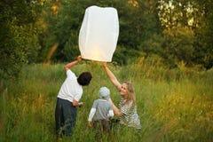 Mutter mit ihren Söhnen, die Papierlaterne fliegen stockbild