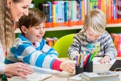 Mutter mit ihren zwei Söhnen, die Zeit in der Bibliothek verbringen Lizenzfreie Stockfotos