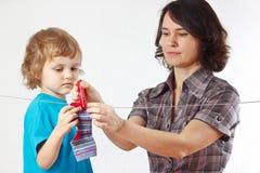 Mutter mit ihrer hängenden Kleidung des kleinen Sohns Lizenzfreie Stockfotos