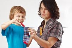 Mutter mit ihrer hängenden Kleidung des Sohns Stockfotografie