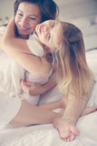 Mutter mit ihrer netten kleinen Tochter auf Bett Stockfotografie