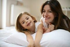 Mutter mit ihrer netten kleinen Tochter, die auf Bett liegt Lizenzfreie Stockfotografie