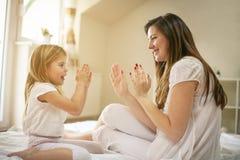 Mutter mit ihrer netten kleinen Tochter, die auf Bett sitzt Lizenzfreie Stockbilder