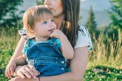 Mutter mit ihrer Tochter auf ihren Knien Stockbild