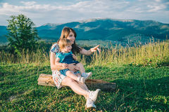Mutter mit ihrer Tochter auf ihren Knien zeigen irgendwo Stockfotos