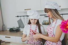 Mutter mit ihrer Tochter bereiten die Brötchen zu stockfoto
