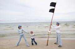 Mutter mit ihrer Tochter, die auf dem Strand spielt Lizenzfreie Stockfotos