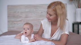 Mutter mit ihrer Tochter, die für die Kamera liegt auf Bett, Elternteil leicht aufwirft, küsst und umarmt ihr neugeborenes Mädche stock video