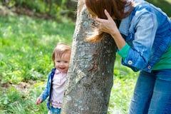Mutter mit ihrer Tochter, die hinter einem Baum sich versteckt Stockbild