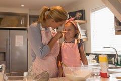 Mutter mit ihrer Tochter, die Nahrung in der Küche zubereitet stockfotos