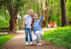 Mutter mit ihrer Tochter, die in Stadtsommerpark geht, zeigen den Finger oben lizenzfreie stockfotografie