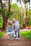 Mutter mit ihrer Tochter, die in Stadtsommerpark geht, zeigen den Finger oben lizenzfreie stockfotos