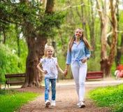 Mutter mit ihrer Tochter gehen in Stadtsommerpark lizenzfreie stockbilder