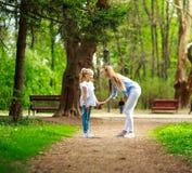Mutter mit ihrer Tochter gehen in Stadtsommerpark lizenzfreies stockbild