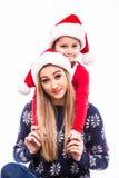 Mutter mit ihrer Tochter im Weihnachtshut Lizenzfreie Stockbilder